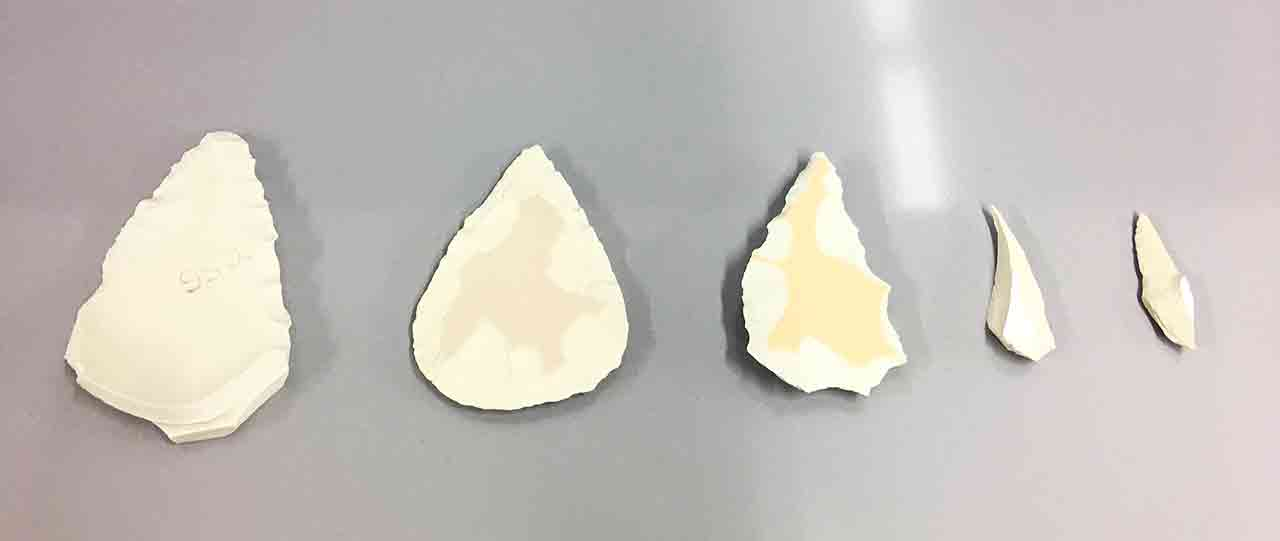 Arrowhead like forms made from shards of toilet ceramic .